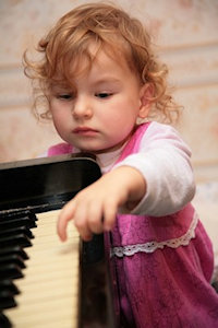 Little girl tentatively touching a piano keyboard